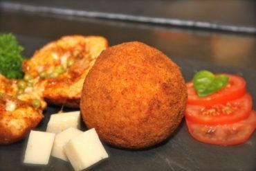 Arancini au du Riz enrobé de panure dorée, Farcie de viande de bœuf, Petits pois, Parmesan, Mozzarella, Tomate, Basilic, (Sauce Bolognaise).